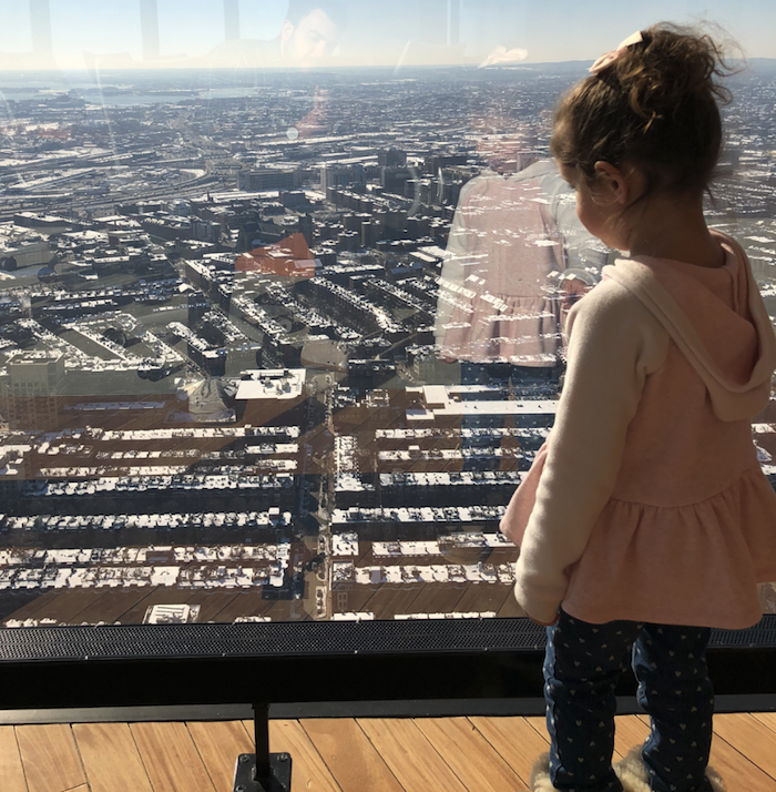 Photo of Henry's daughter looking out the window of a skyscraper.